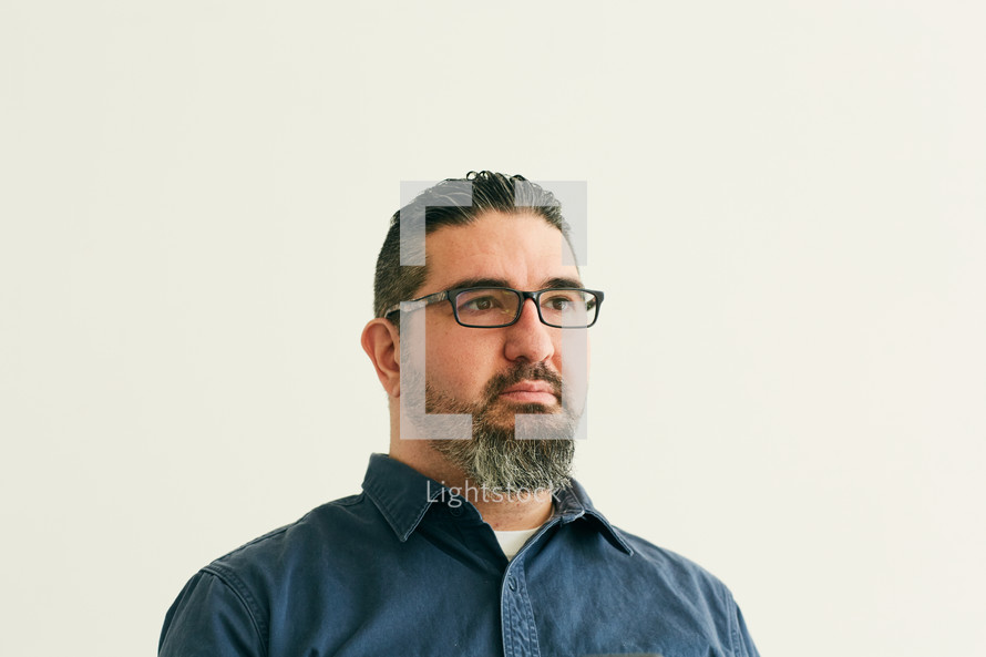 stoic man in reading glasses