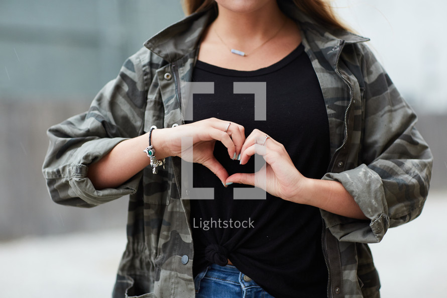 teen girl making a heart symbol with her hands