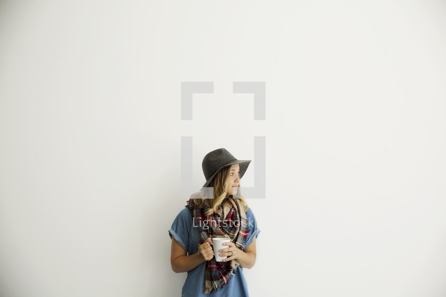 a woman with a plaid shaw and hat holding a mug