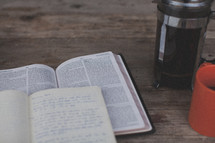 An open Bible and notebook next to an orange coffee mug and french press