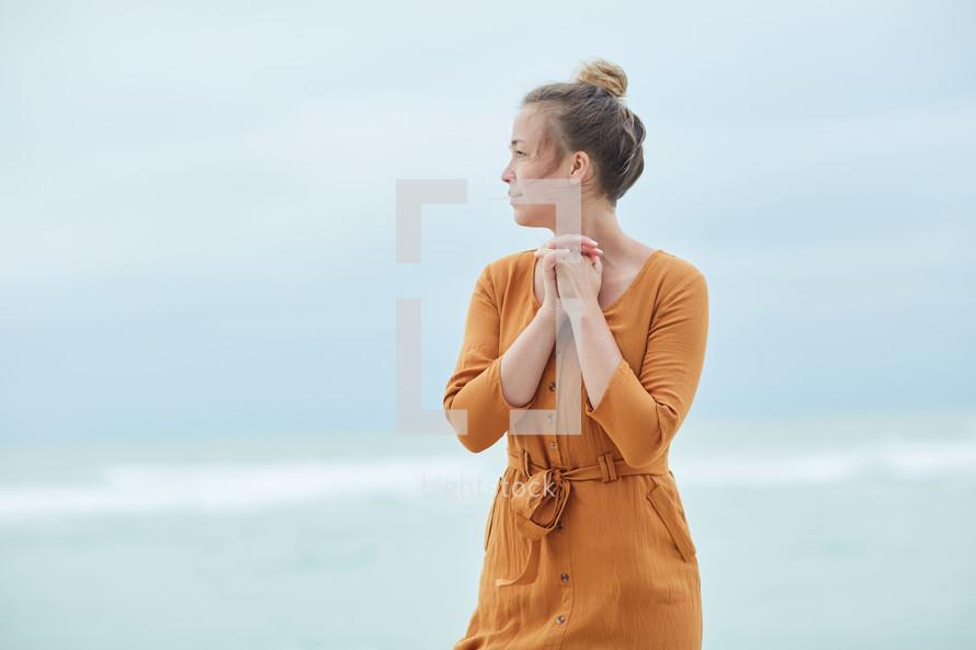 a woman standing on a beach praying