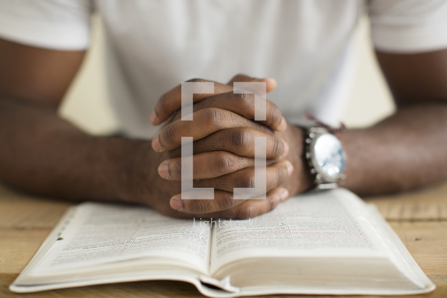 a man with praying hands over the pages of a Bible.