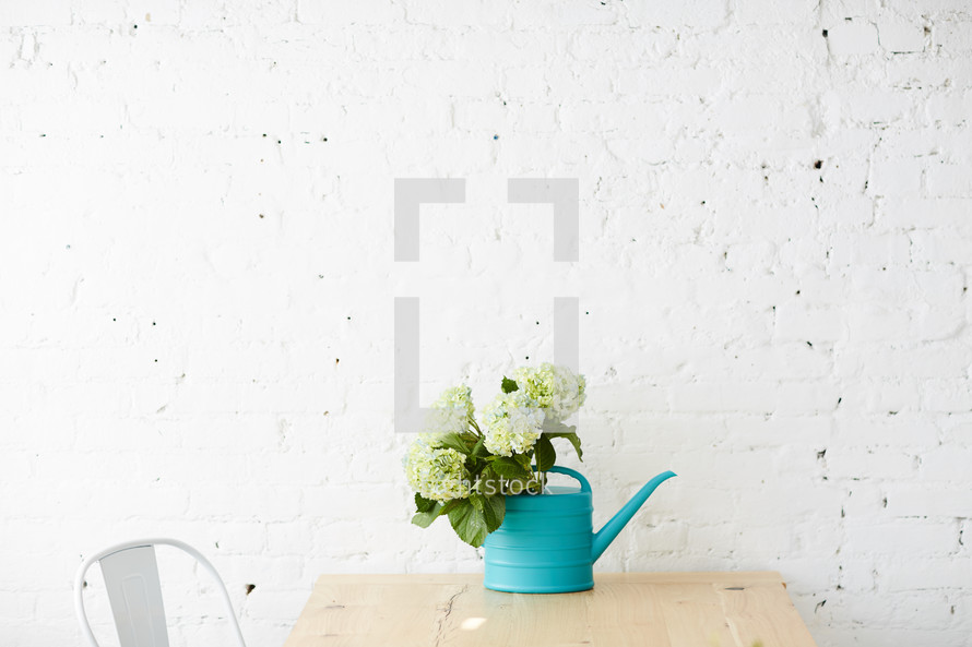 hydrangeas in a watering can on a table