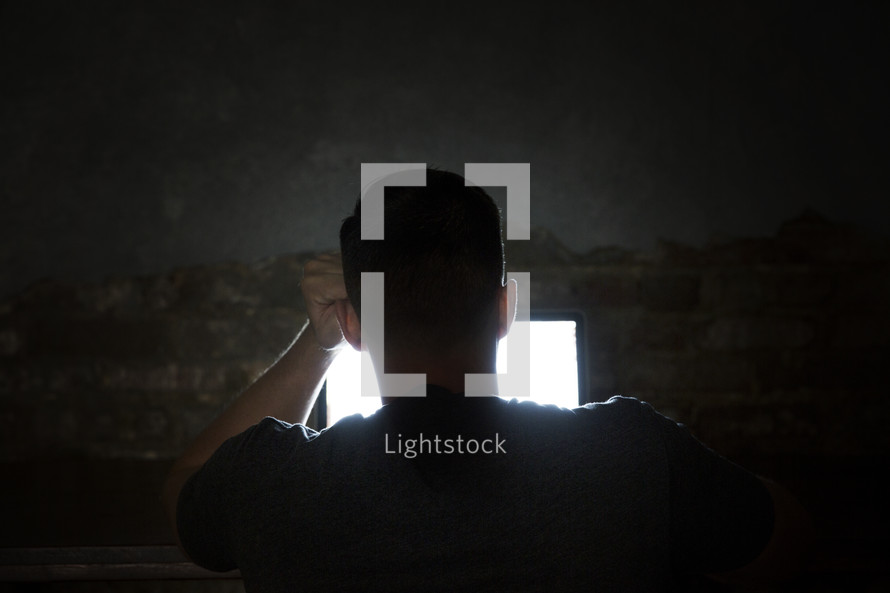 man looking at a computer screen in darkness