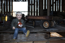 A toddler boy and an old radio flyer wagon.