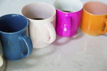 row of colorful coffee mugs