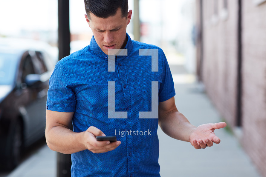 a frustrated man looking at his cellphone