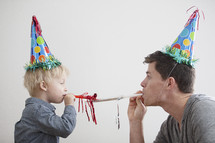 A man and toddler boy wearing party hats.