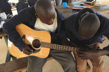Man teaching a boy to play guitar.