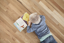 A toddler boy lying on a wood floor reading a book.