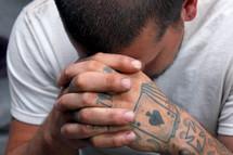 tattooed hands praying