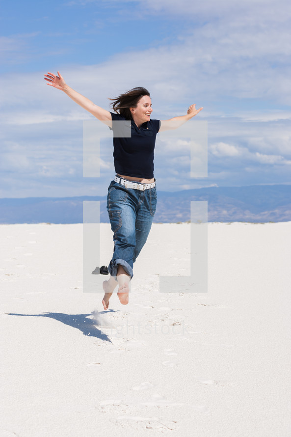 Woman Jumping and Feeling Free in the Desert