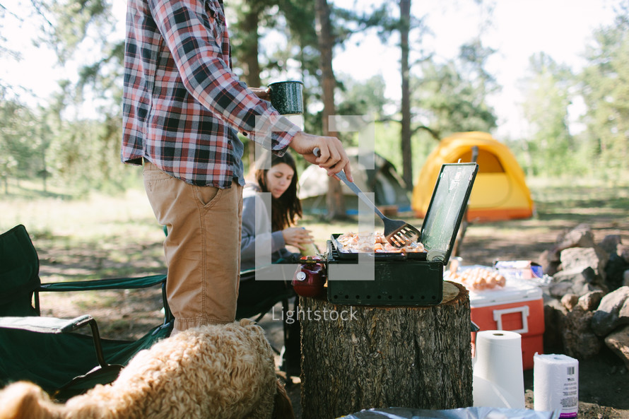 a man cooking breakfast while camping