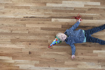 a toddler boy lying on a wood floor wearing a party hat.
