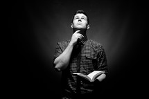 man holding a Bible with his hand under his chin looking up to God
