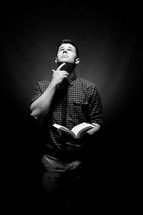man holding a Bible with his finger under his chin and looking up to God
