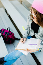 Teenage girl back to school studying, ready bible, campus, on bleachers,  devotional