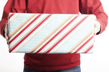 A man holding out gift wrapped in striped wrapping paper