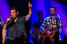 youth pastor praying during a worship service, with tattooed arm