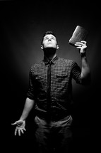 man holding a Bible up and looking to God for answers