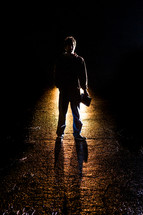 Silhouette of a man holding a Bible standing in front of a light in the darkness.