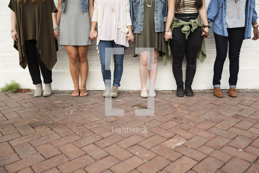 Legs of a group of female friends.