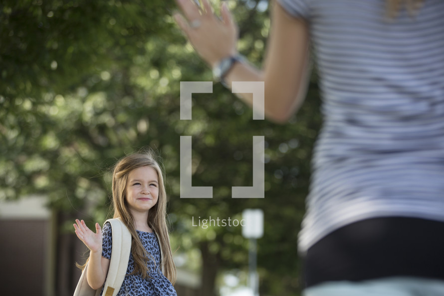 a little girl with a book bag waving goodbye to mom on the first day of school