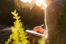 a woman journaling outdoors at sunrise.
