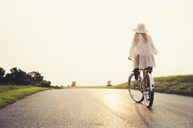 woman riding a bicycle on a road