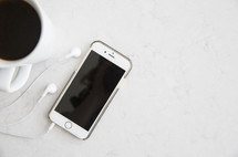 coffee mug, iPhone, earbuds on a white background