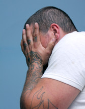 man with tattooed hands covering his face