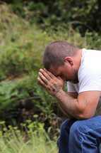 man with tattooed hands praying