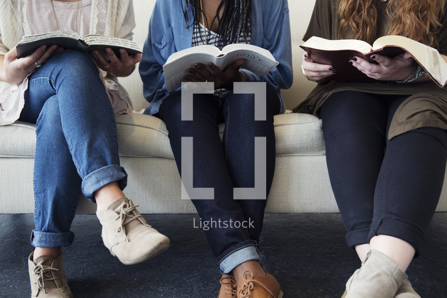 young women sitting on a couch talking, laughing, and reading bibles.