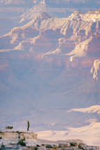 a woman standing at the edge of a cliff looking out at canyons