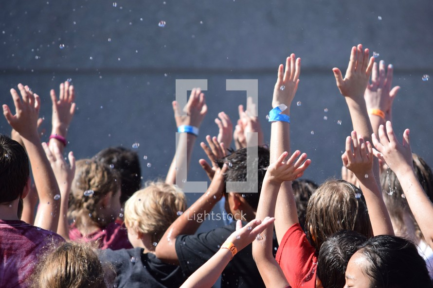 kids with hands raised getting wet from splashing water at summer camp