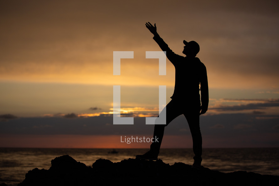 silhouette of a man with hand raised standing on a shore