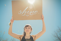 woman holding up a sign in sunlight with the words shine
