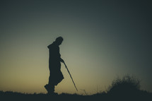 man in a robe with a walking stick