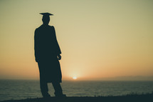 silhouette of a graduate on a beach at sunset