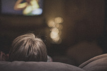 A person sitting on the couch watching tv