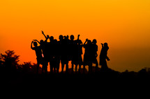 silhouettes of children with raised hands at sunset