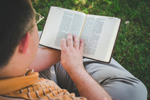a man sitting in the grass on a sunny day reading a Bible God's Word with a view of him
