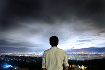 man with his back to the camera looking out over a city at night