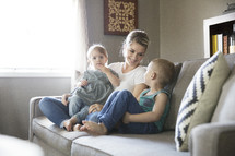 a mother sitting on the couch with her children