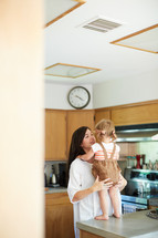 a mother holding her toddler daughter in the kitchen