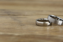 Two men's wedding rings on a wooden table.