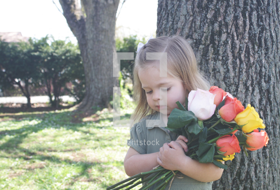 a little girl holding a bouquet of roses for mom