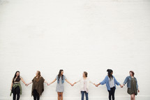 Six young women holding hands in a line in front of a white brick wall.
