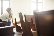 a woman sitting in a church pew praying