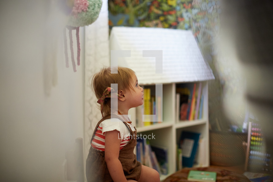 a toddler girl in a playroom
